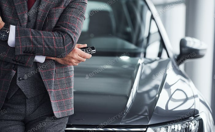 Man in modern formal clothes stands against black car with keys in hand