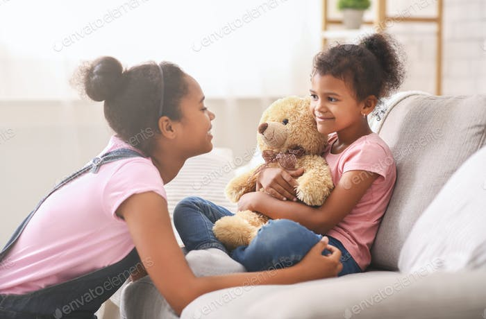 Black teen girl playing with her little sister at home