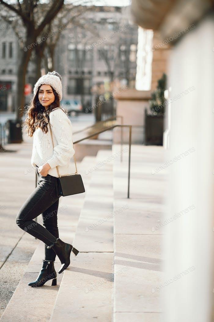 Cute brunette in a white sweater in a city