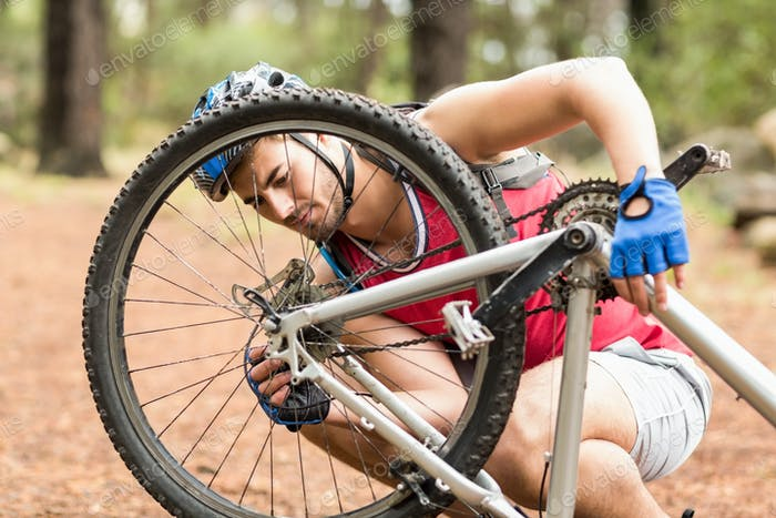 Happy handsome biker repairing bike in the nature