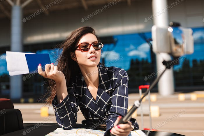Beautiful girl in sunglasses with map leaning on cabriolet car w