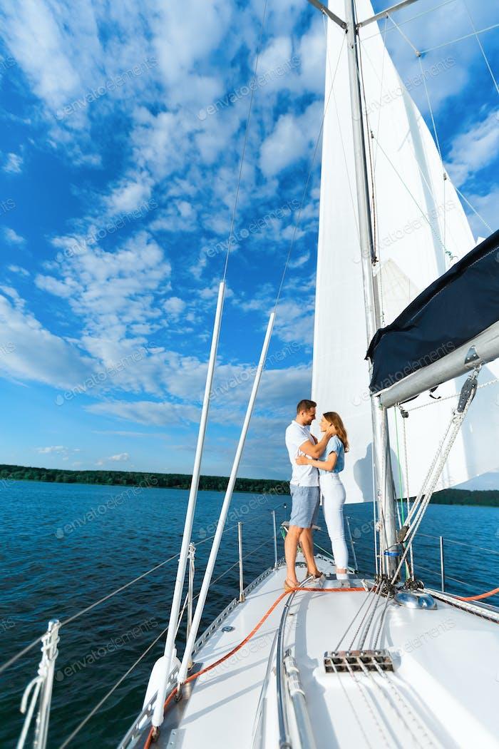 Couple On Yacht Hugging Sailing At Seaside, Enjoying Vacation, Vertical