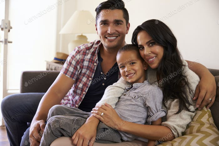 Portrait Of Happy Family Sitting On Sofa In at Home