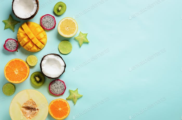 Exotic fruits on pastel blue background - papaya, mango, pineapple, banana, carambola, dragon fruit