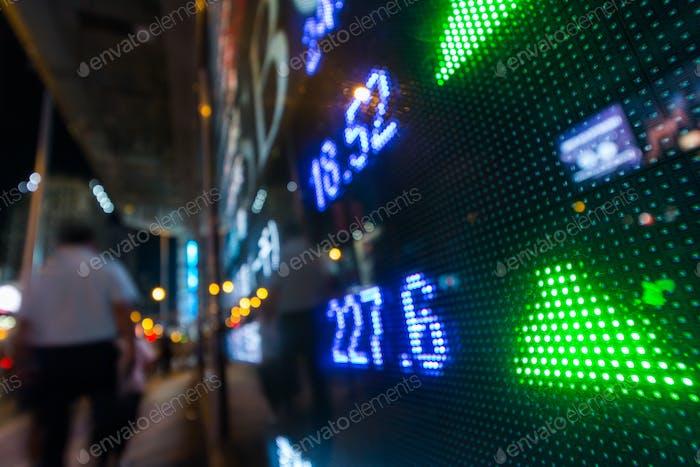 Las cotizaciones del mercado de valores con la escena de la ciudad reflejan en el vidrio