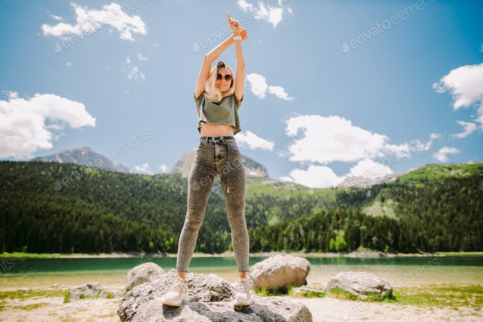 attractive woman posing in mountains with lake view