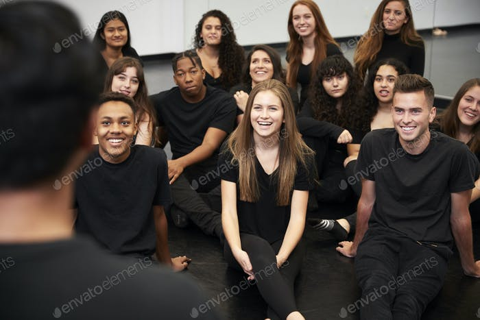 Teacher At Performing Arts School Talking To Students Sitting On Floor In Rehearsal Studio