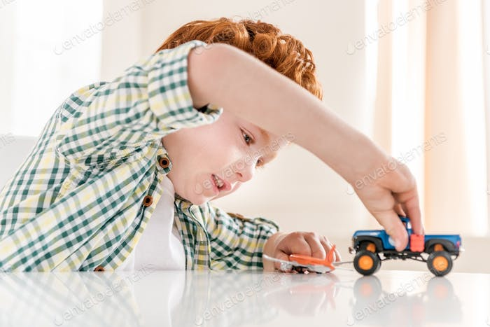 side view of little boy playing with toys at home