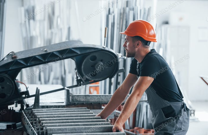Operator of machine. Industrial worker indoors in factory. Young technician with orange hard hat