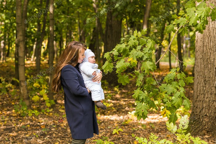 Beautiful lifestyle autumn photo mother and child walks in the park, warm sunlight