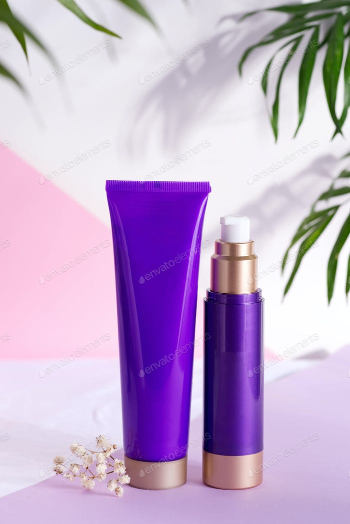 Purple cosmetic plastic bottles for cream and lotion with green herbal leaves and flowers on a