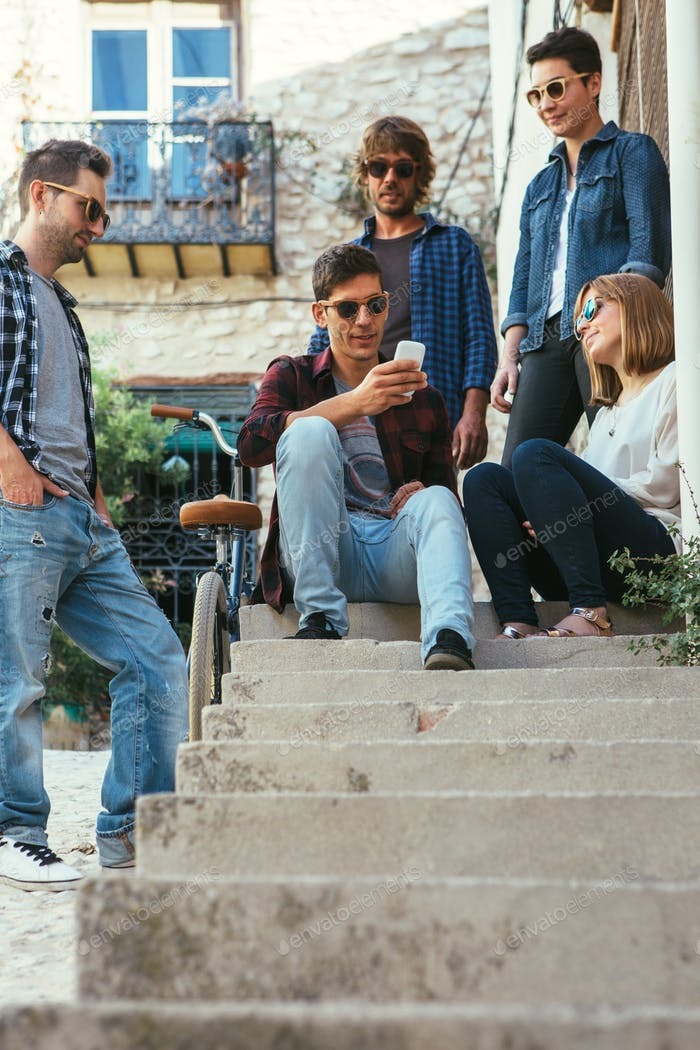 Group of stylish friends with smartphone