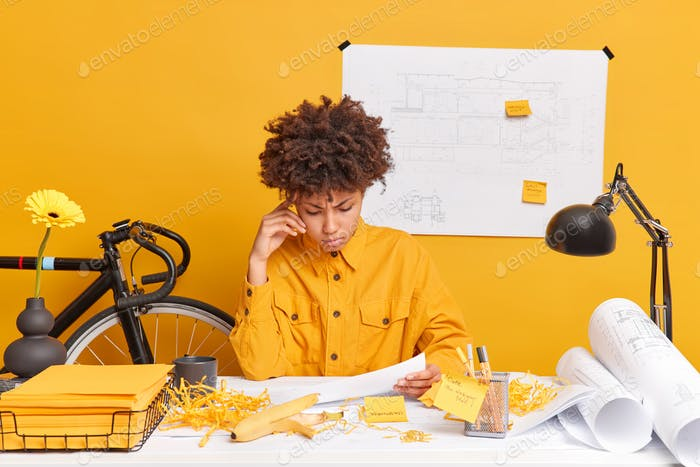Serious African American female student of engineering faculty looks attentively at papers thinks ab