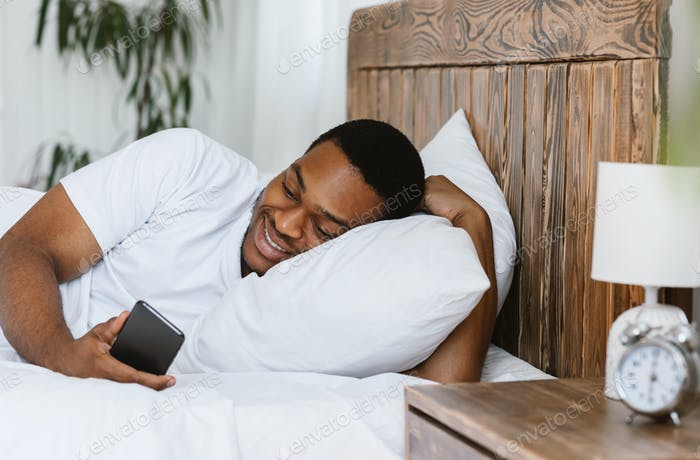 Happy African Man Using Phone Browsing Internet Lying In Bed
