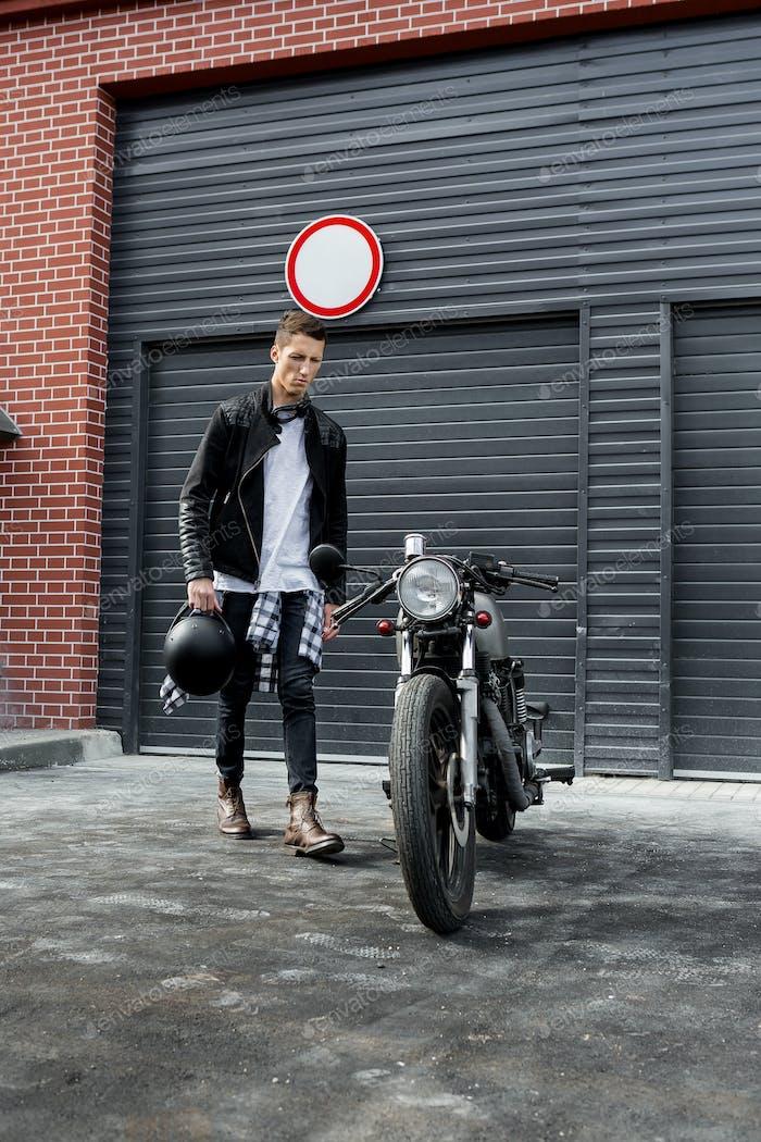 Brutal man near his cafe racer custom motorbike.