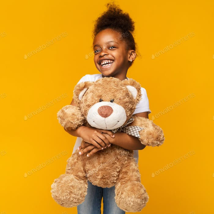 Nettes schwarzes Mädchen umarmen großen Spielzeug Teddybär