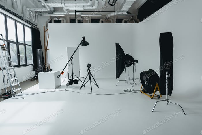 photo studio with digital photo camera on tripod, lighting equipment and fan