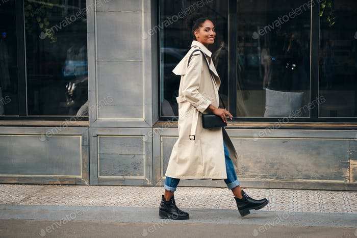 Smiling African American girl in trench coat happily looking in camera walking down the street