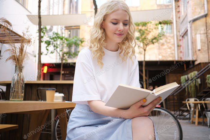 Beautiful romantic blond girl dreamily reading book in courtyard of cafe
