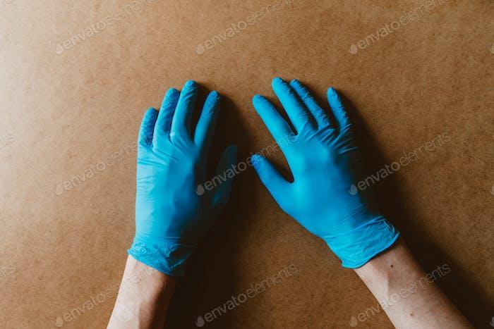 Hände in blauen Schutzhandschuhen aus Gummi auf beige Hintergrund