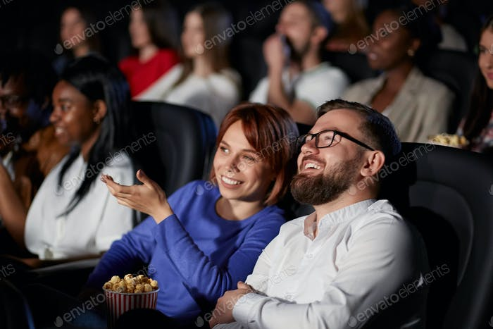 Couple discussing film in movie theater