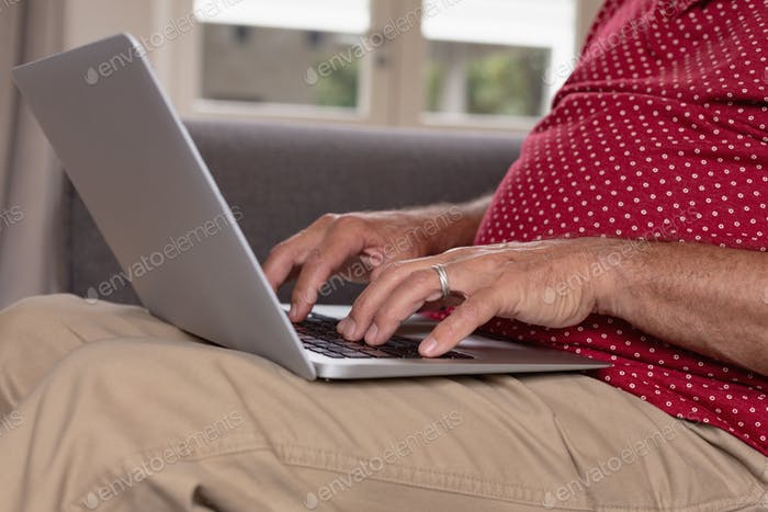 Mid section of active senior Caucasian man using laptop on sofa in a comfortable home