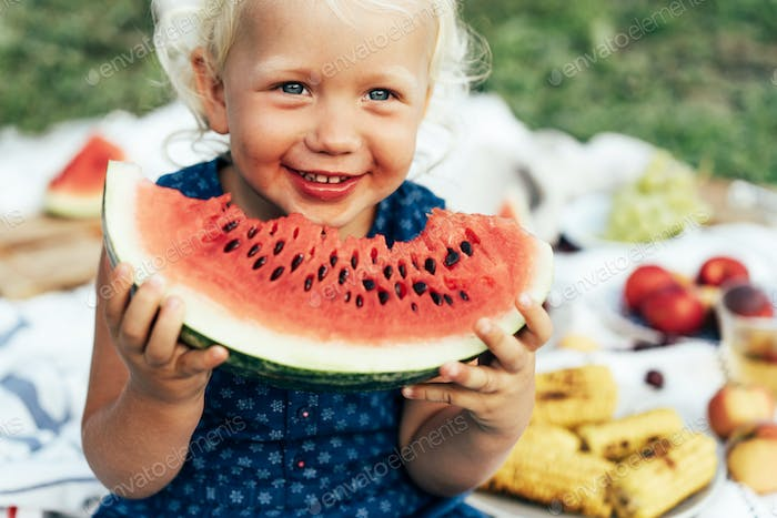 Little blond girl holding a big watermelon slime and having fun, summer food,
