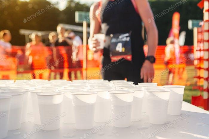 Tisch mit Tassen Wasser bei Sportveranstaltung