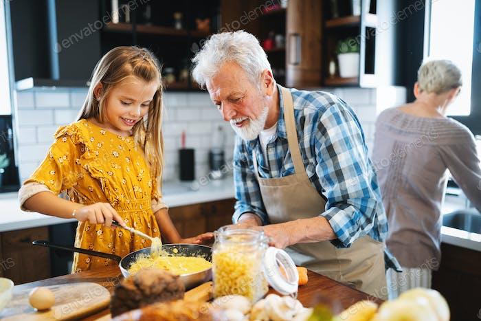 Lächelnder Großvater hilft Kindern, in der Küche zu kochen