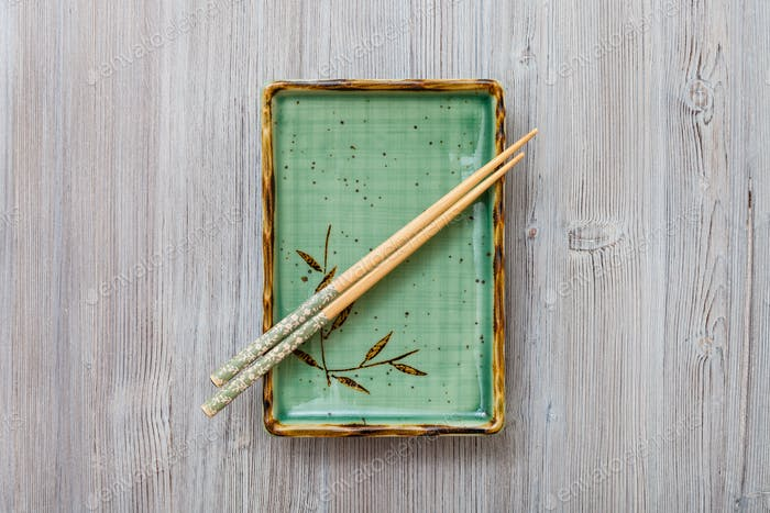 above view of square plate with chopsticks on gray