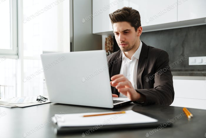 Serious young businessman working indoors.