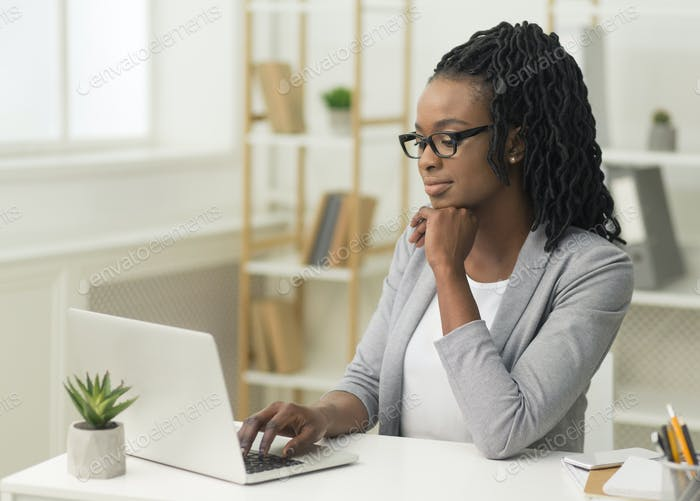 Pensive Afro Businesswoman Typing On Laptop In Modern Office