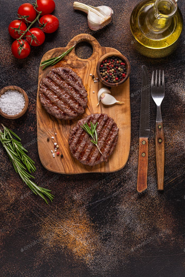 Fried cutlet for burger on a wooden board.