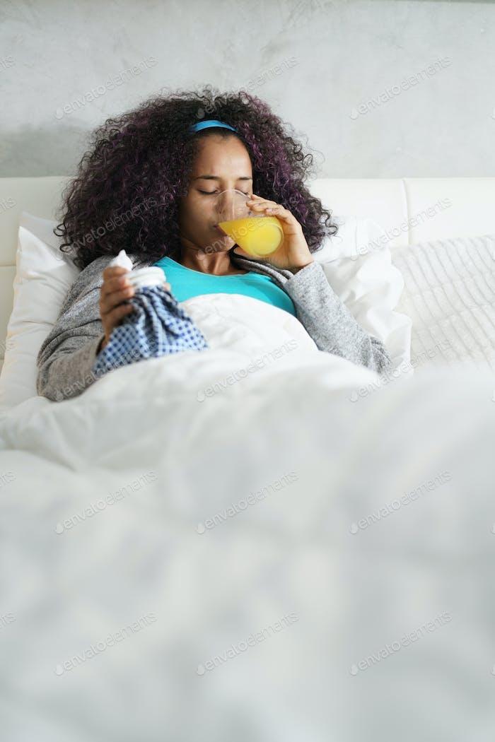 schwarz frau mit grippe und kalt halten eisbeutel