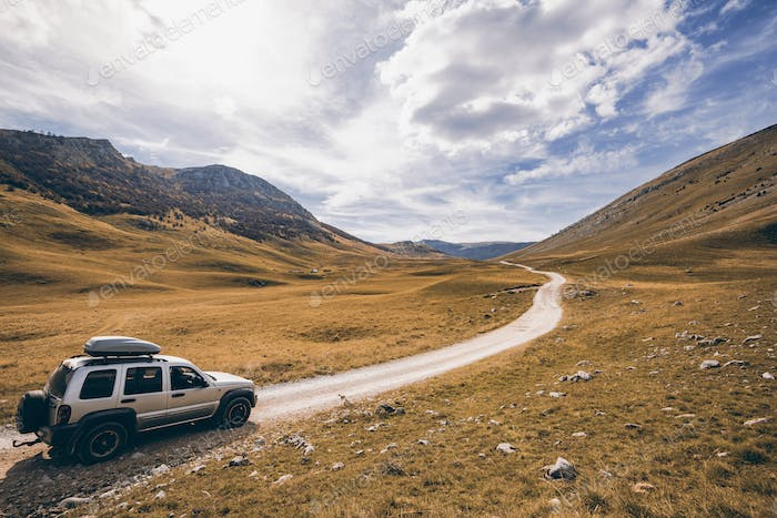 Off road car drives in rural steppe in Bosnia