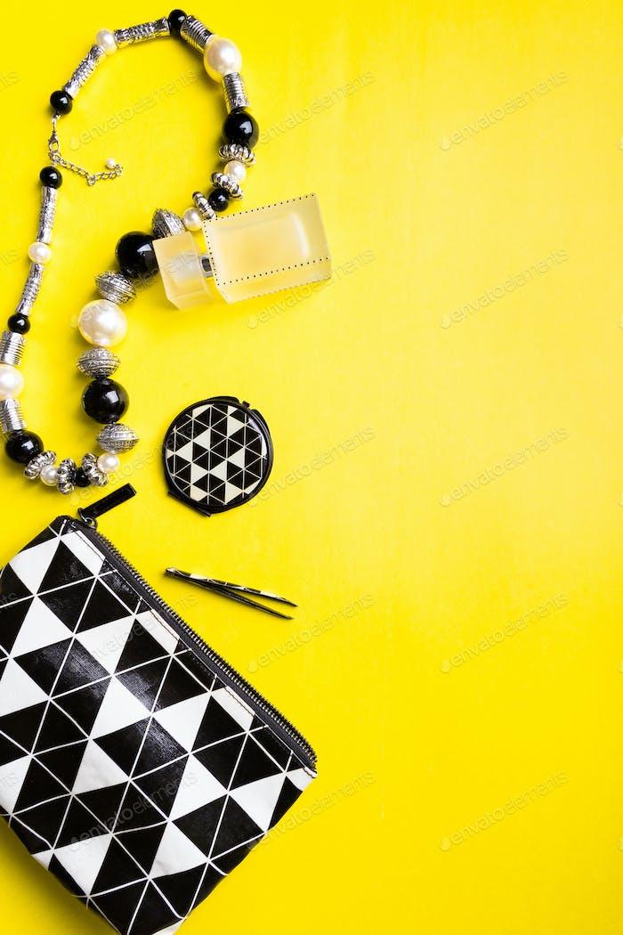 Bolso de mano de Mujer con maquillaje y accesorios sobre Fondo amarillo. Lazo plano.