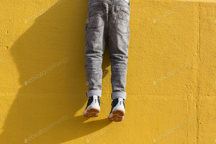 Legs of young boy in grey jeans against yellow wall