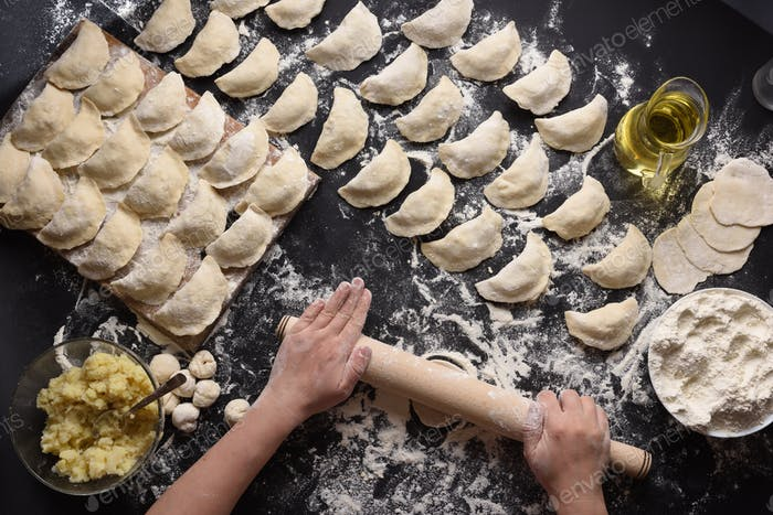 Woman sculpts dumplings with handmade potatoes on a black background. Shot from the top angle.