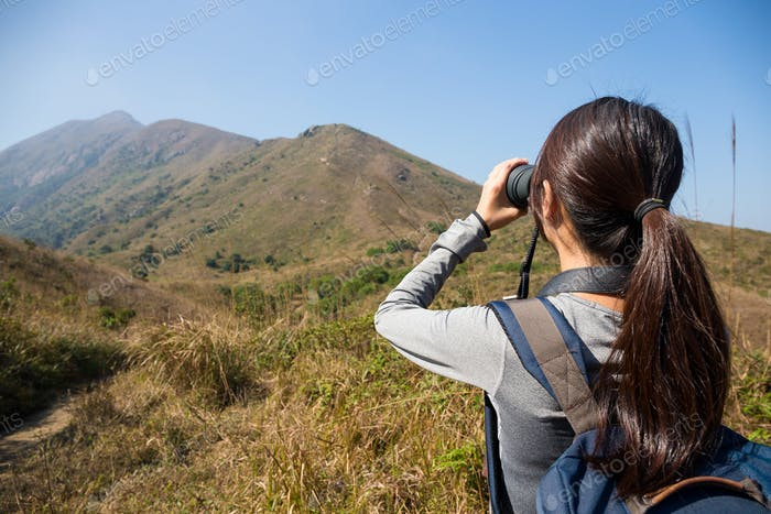Back view of woman looking through binoculars