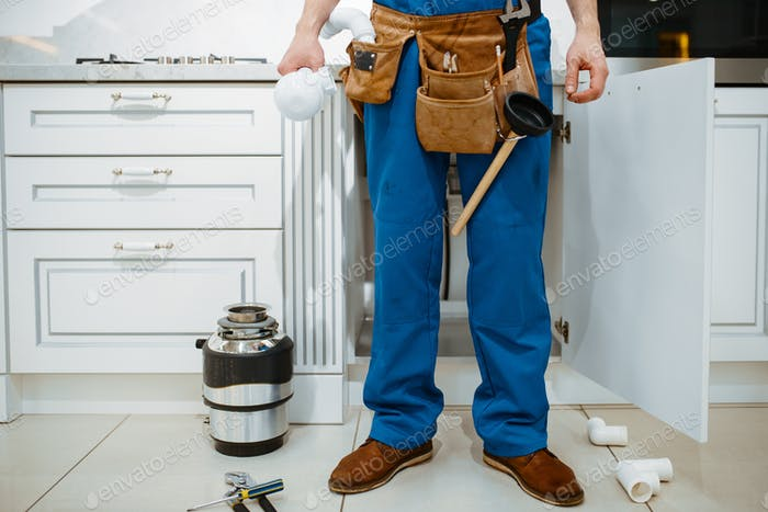 Male plumber installing water filter in kitchen
