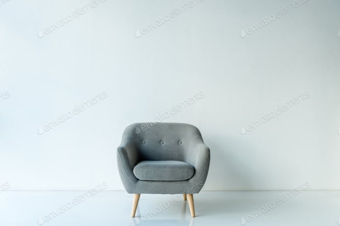 Empty armchair in the middle of the room on floor