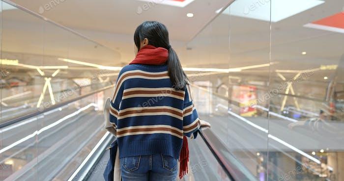 Frau nehmen Rolltreppe im Einkaufszentrum