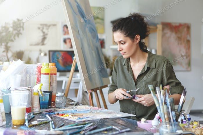 Young female painter sitting at table surrounded with various paint brushes and watercolors while cr