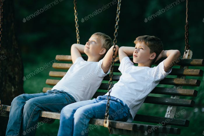 little boys dreaming on swing