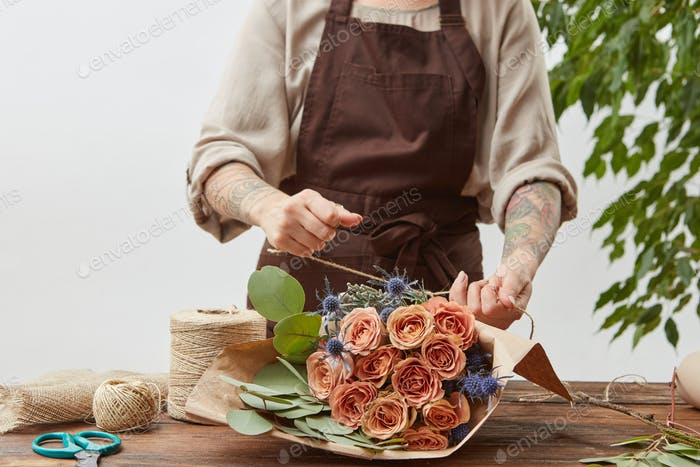 Florist workplace - woman's hands are arranging a new bouquet with roses and decorative green