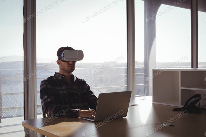 Businessman using virtual reality headset and laptop in office