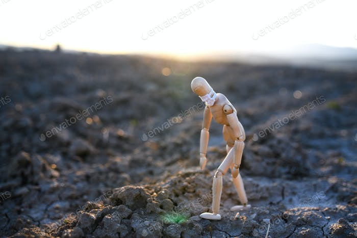 Tired wooden mannequin with face mask on dry soil, corona virus, death and life concept