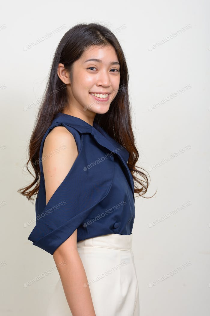 Profile view of happy young beautiful Asian businesswoman looking at camera