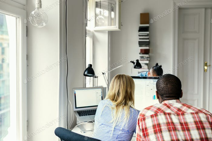 Editors using computer together in office