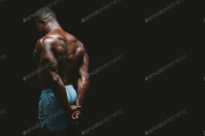Rear view of side triceps pose perfomed by afro bodybuilder